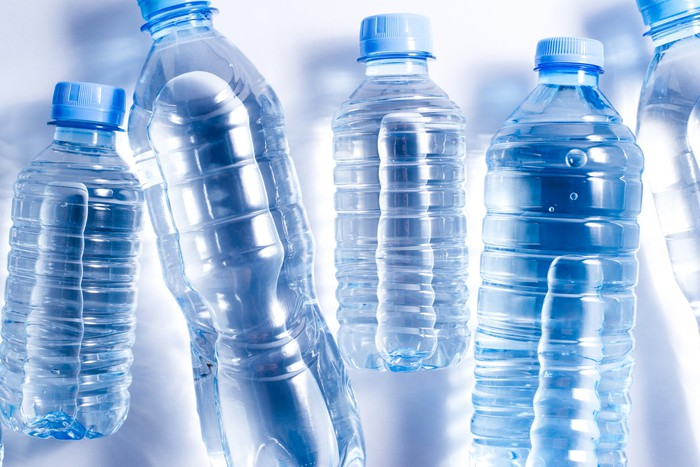 Spring water in blue-tinted plastic bottles, lying on a white surface.
