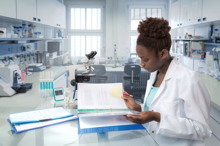 A scientist considers a binder of paperwork in the laboratory.
