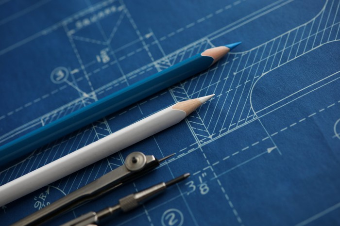 A blueprint with pencils on top.