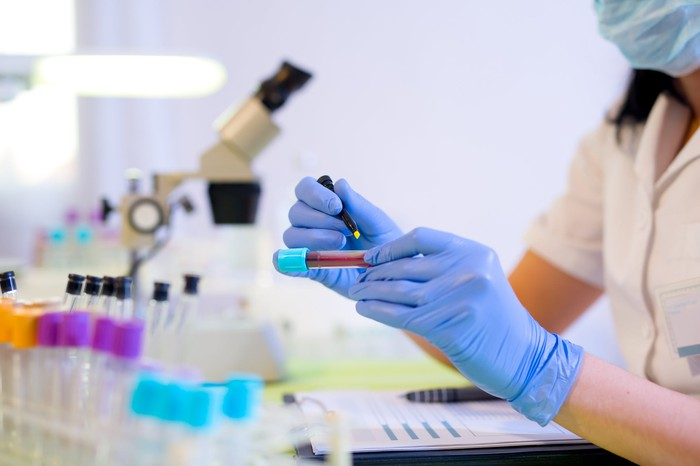 Person in a lab holding a vial next to a microscope