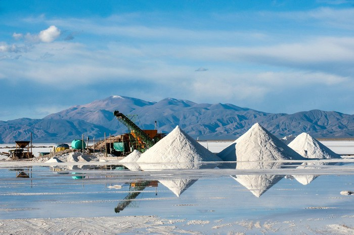 Equipment and piles of lithium salts in a desert landscape with mountains behind.