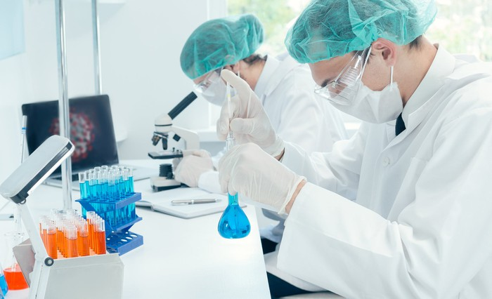 Two scientists work in a laboratory, side by side.