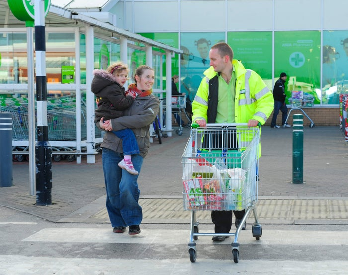 A customer and an Asda employee walk out of an Asda grocery store.