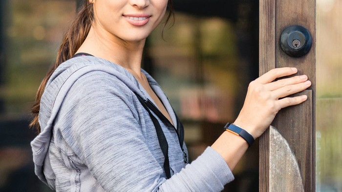 A lady holding a door open with her Fitbit tracker on her wrist.