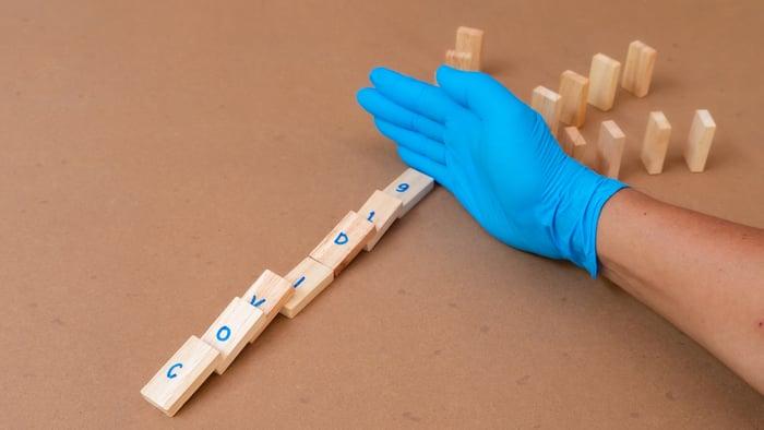 Gloved hand stop wooden domino spelling