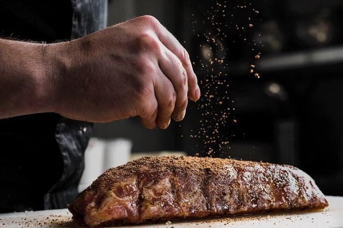 A home chef sprinkles seasoning on a steak.