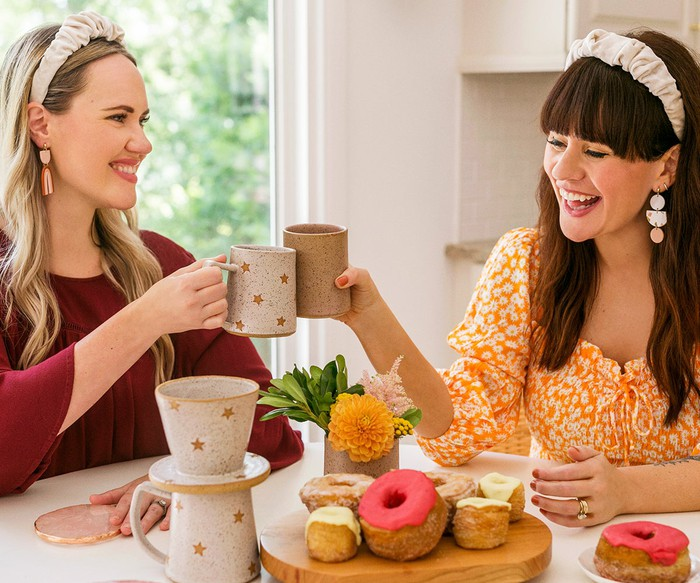 Two smiling women at a kitchen table clinking retro coffee mugs.