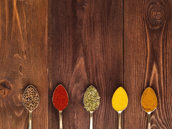Five spoons filled with colorful spices rest on a wooden table.