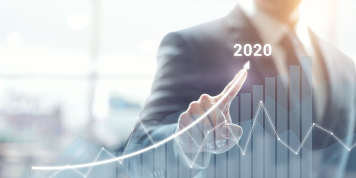 business man drawing digital arrow up with 2020 showing, indicating gains this year