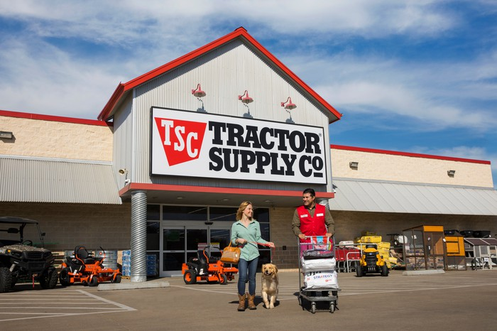 Tractor Supply employee walking a woman and her dog out to their car with supplies