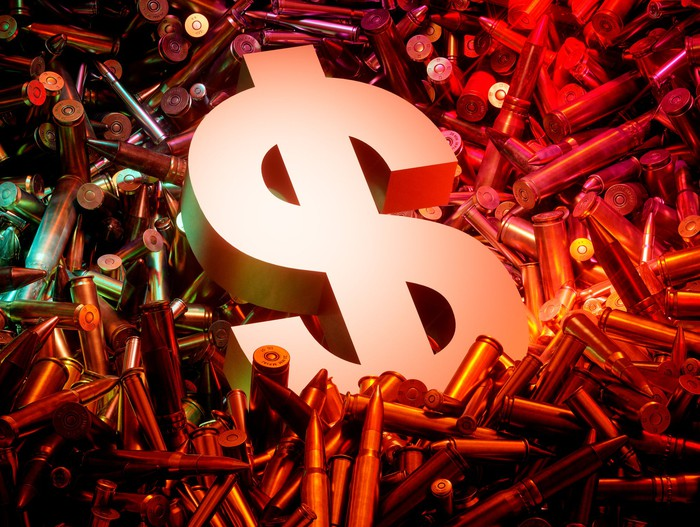 Dollar sign on pile of ammunition casings