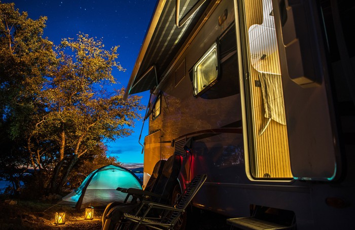 An RV and a nearby pitched tent are seen at night.