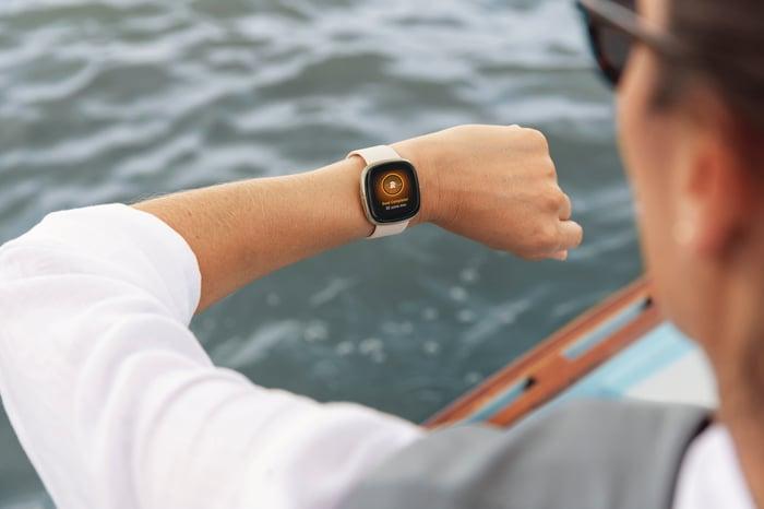 Man looking at a Fitbit Sense