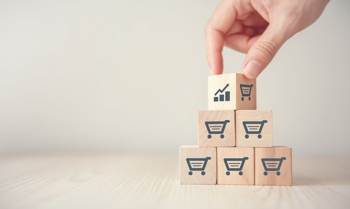A person stacking blocks featuring shopping cart and chart icons.