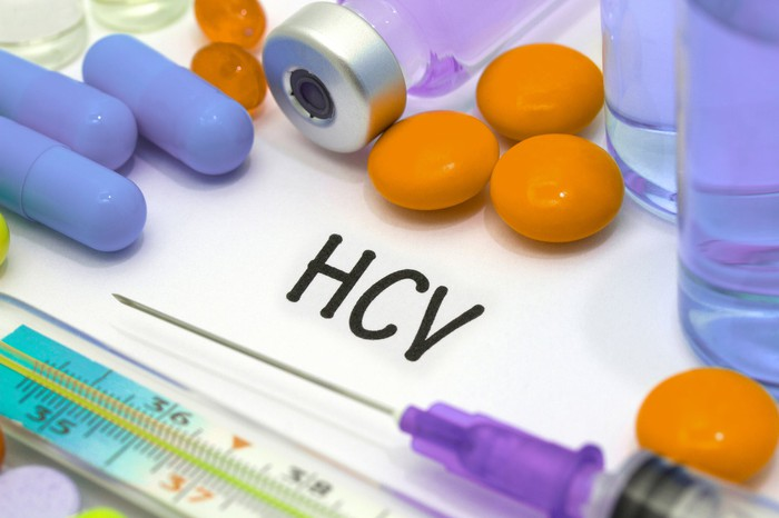 several different colored pills, a syringe, and the letters HCV on paper