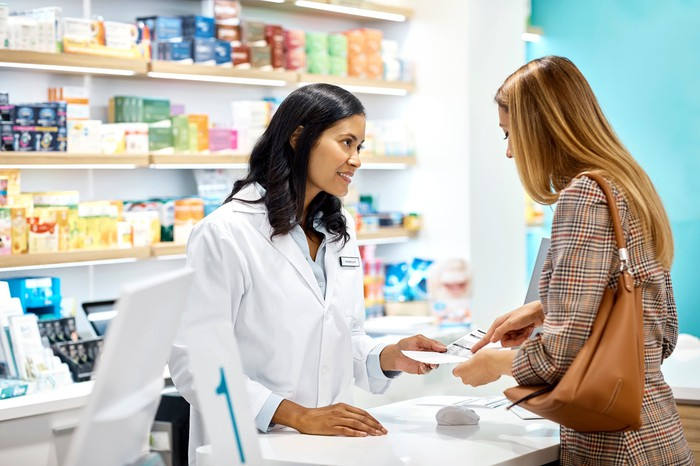 A pharmacist standing in front of shelves of prescriptions, helping a woman at the counter.