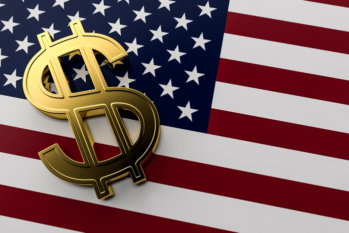 A golden dollar sign on an American flag.