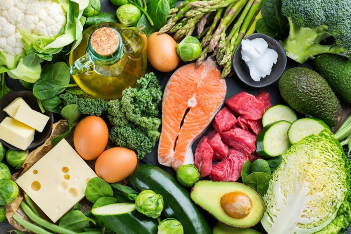 """An assortment of raw fish, meats, vegetables, cheese, eggs, and fruit, representing a """"Keto"""" diet."""