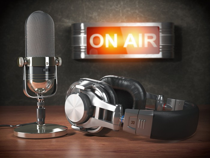 A microphone and headphones next to a lit sign saying on air.