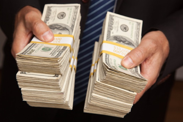 A businessman handing over stacks of one hundred dollar bills.