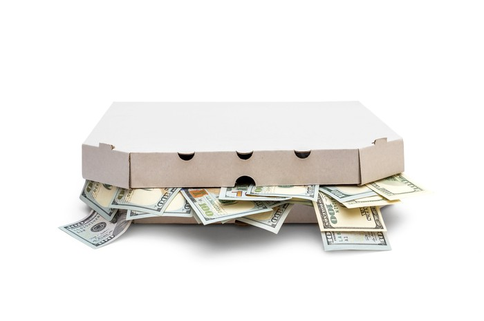 A pizza box is stuffed with money.