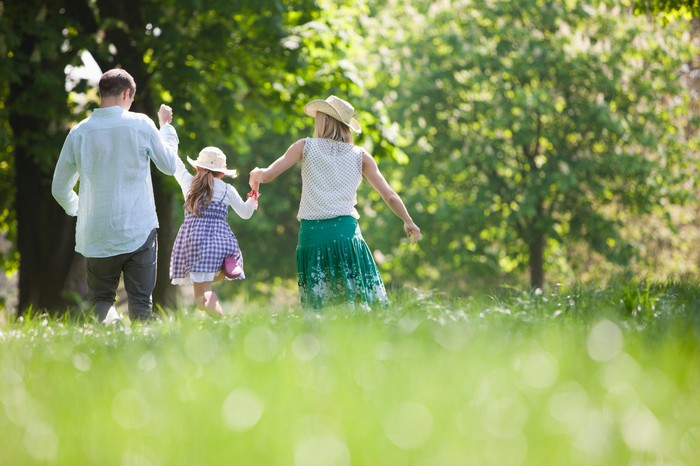 A family walks through a park hand in hand.