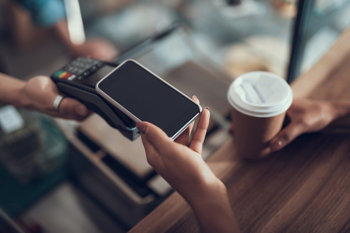 A person touches their smartphone to a card reader at checkout in a coffee shop