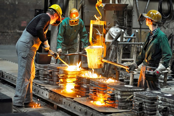 Three workers pour and shape molten steel on a production line.