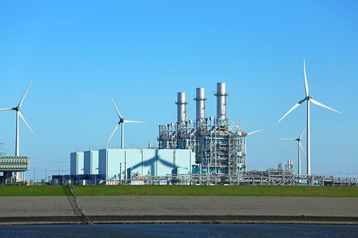 A gas-powered energy plant and wind turbines