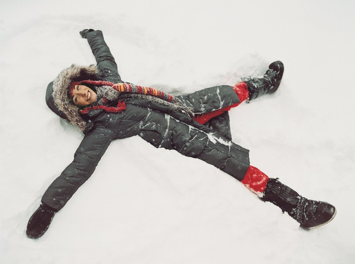 A woman in a parka lies in the snow making a snow angel