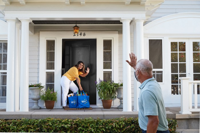 Walmart customer picking up a delivery off her front porch as the delivery person waves from a distance.