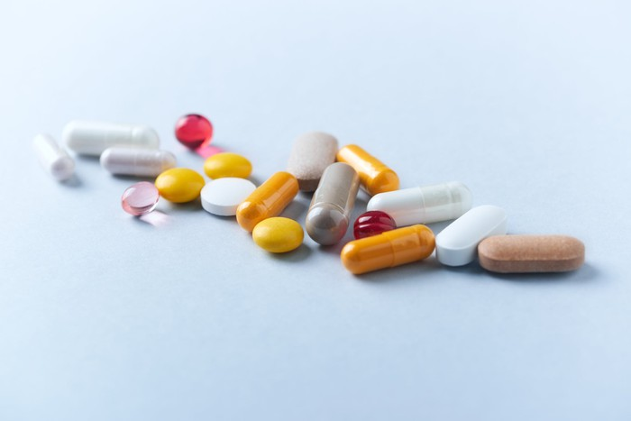 A scattering of pills of different shapes, sizes, and colors.