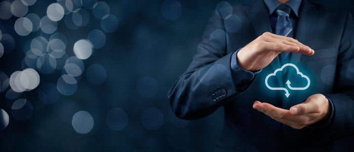 A man in a suit with his hands cupping a cloud computing icon with a bokeh effect in the background.