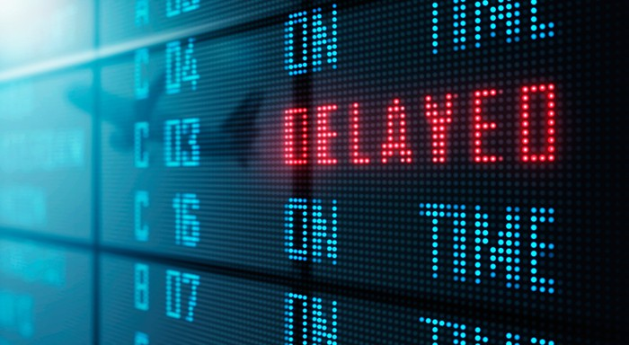 Airport flight schedule board reads DELAYED