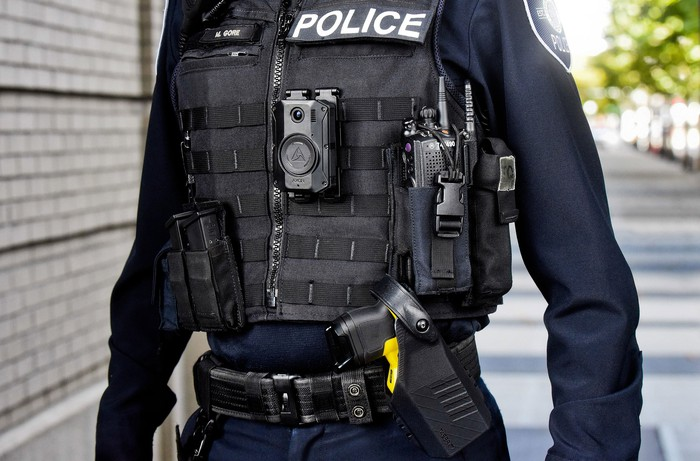 Police officer in gear, including a Taser 7 and Axon body camera from Axon Enterprise
