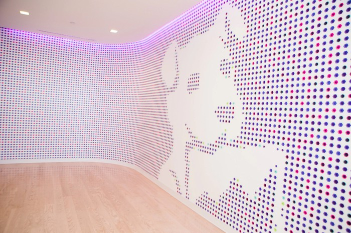 Datadog logo of a dog holding a rectangular graph, put on a lobby wall.