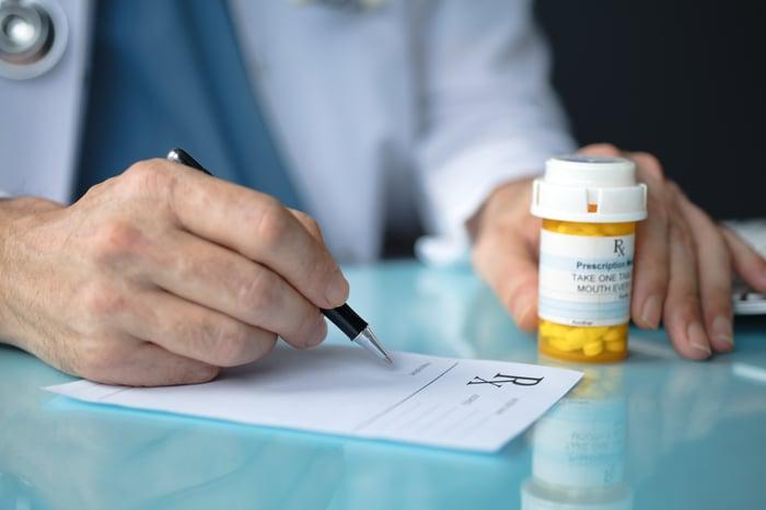 Doctor fills out prescription form, full pill bottle besides him