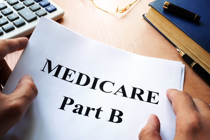 Person holding document that says Medicare Part B with calculator, book, and pen nearby on wooden surface