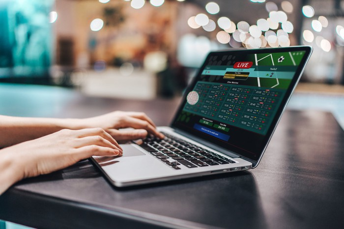 A sports betting site visible on a laptop screen, with a woman's hands on the keyboard.