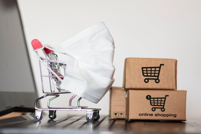 """A miniature grocery cart covered by a face mask runs into a stack of tiny cardboard boxes labeled """"online shopping."""""""