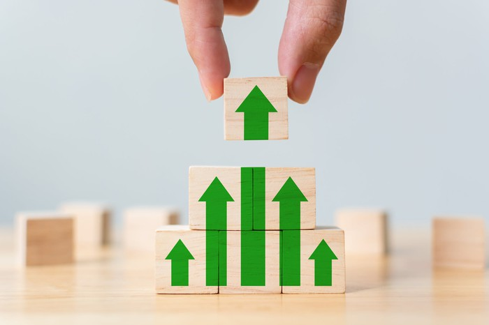 man stacking building blocks forming upward arrows that represent stock growth