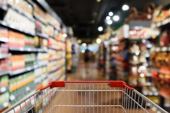 A first person point of view of a shopping cart being pushed down a grocery aisle.