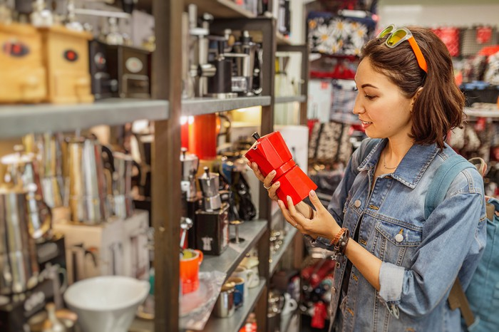 woman shopping for home merchandise holding red coffee press