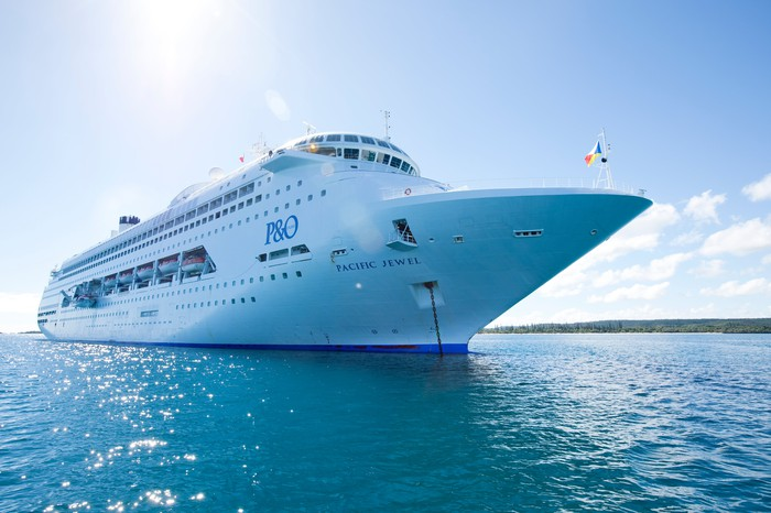 """A waterline view of the Carnival ship """"Pacific Jewel"""" on blue waters under a sunny sky."""