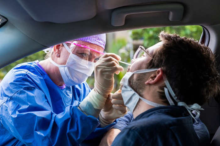 Technician administers a nasal swab coronavirus test to a man sitting in his car.