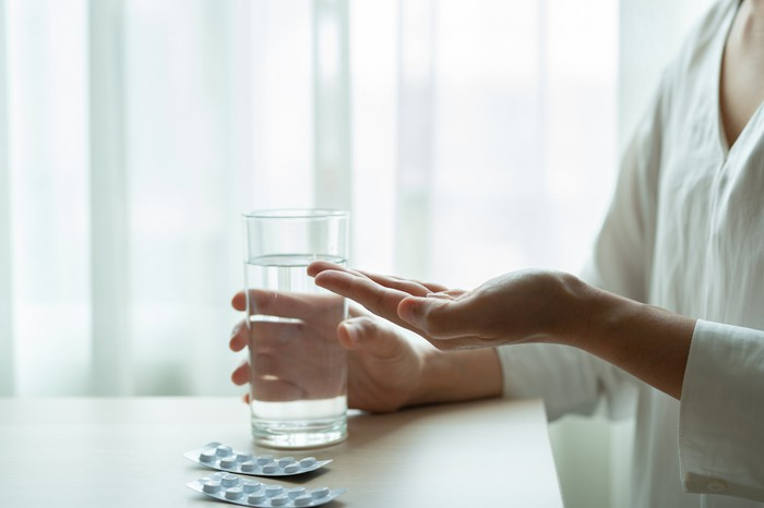 A person at a table with a pack of pills and one in her hand with a glass of water in the other hand.