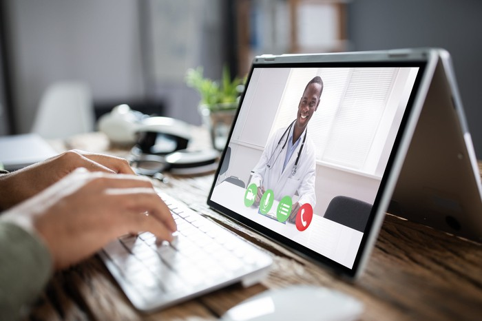 A man typing on a keyboard with a tablet up as he meets with his doctor through a virtual visit.
