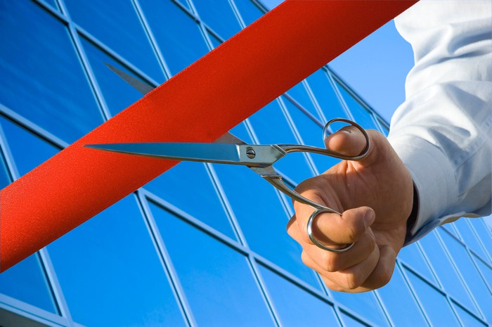 A man's hand holding a pair of scissors cutting a red ribbon outside an opening business location.