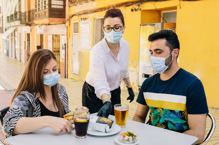 A waitress serves people at an outdoor restaurant while all wear masks.