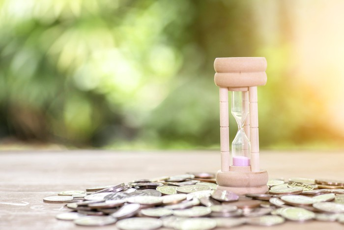 Pink hourglass with coins scattered around it.